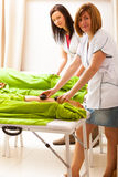 Beauty salon. Women getting spa hot stone legs massage Royalty Free Stock Images
