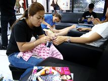 A beauty salon worker gives a customer a manicure and pedicure. Royalty Free Stock Photos