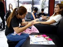 A beauty salon worker gives a customer a manicure and pedicure. Stock Image