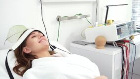 Beauty salon. Young attractive girl in a cosmetic salon lying on the table takes electro therapy