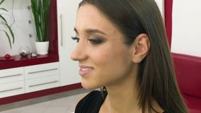 Beauty salon. Young beautiful girl model sitting in the chair. Makeup artist makes makeup girls.  stock video footage