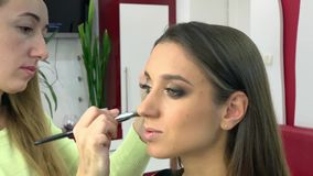Beauty salon. Young beautiful girl model sitting in the chair. Makeup artist makes makeup girls.  stock video