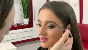 Beauty salon. Young beautiful girl model sitting in the chair. Makeup artist makes makeup girls stock video