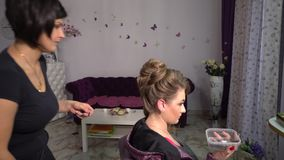 Beauty saloon. Young beautiful girl at the hairdresser. Hairdresser makes the girl hairstyle. Blonde in a beauty salon. 4K stock video footage