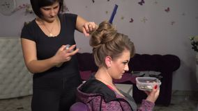 Beauty saloon. Young beautiful girl at the hairdresser. Hairdresser makes the girl hairstyle. Blonde in a beauty salon. 4K stock footage