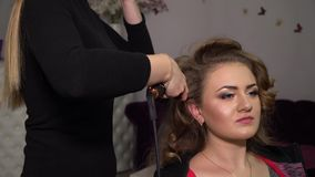 Beauty saloon. Young beautiful girl at the hairdresser. Hairdresser makes the girl hairstyle. Blonde in a beauty salon. 4K stock video