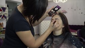 Beauty saloon. Young beautiful girl model is sitting in the chair. Makeup artist makes girl makeup. Makeup artist. Applies eyebrow shades on model`s face. 4K stock video footage