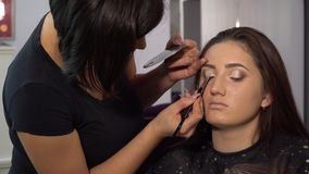 Beauty saloon. Young beautiful girl model is sitting in the chair. Makeup artist makes girl makeup. Makeup artist. Applies shadows on the eyelids of the model stock video footage