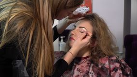 Beauty saloon. Young beautiful girl model is sitting in the chair. Makeup artist makes girl makeup. Blonde in a beauty. Salon. Master puts the girl false stock video footage