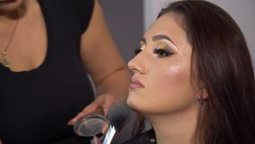 Beauty saloon. Young beautiful girl model is sitting in the chair. Makeup artist makes girl makeup. Brunette in a beauty. Salon. Makeup artist imposes face stock video footage