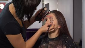 Beauty saloon. Young beautiful girl model is sitting in the chair. Makeup artist makes girl makeup. Makeup artist. Applies shadows on the eyelids of the model stock footage