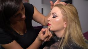 Beauty saloon. Young beautiful girl model sitting in the chair. Makeup artist makes makeup girls. Blonde in a beauty. Salon. Makeup artist paints lips model. 4K stock video footage