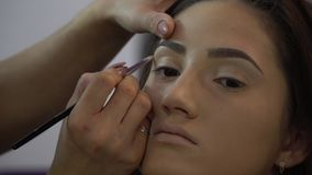 Beauty saloon. Young beautiful girl model is sitting in the chair. Makeup artist makes girl makeup. Makeup artist puts. Highlighter on model face. 4K stock video