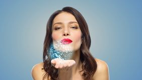 Beautiful woman blowing to low poly projection. Beauty, science and nano technology concept - beautiful woman with red lipstick blowing to low poly shape royalty free stock photos