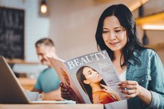 Concentrated woman reading a magazine. Beauty secters. Concentrated women sitting in a cafe and reading a magazine stock images