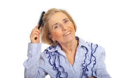 Beauty senior woman brushing hair Stock Photography