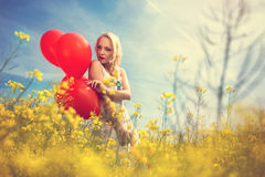 Beauty sensual woman  in the meadow. Enjoy nature with balloons Royalty Free Stock Image