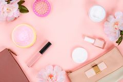 Beauty set with decorative cosmetics. nail polish, brushes and bag on pink background top view mockup. royalty free stock photography