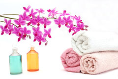 Beauty set with towels. A composition of body oils, towels and a beautiful orchid Royalty Free Stock Photo