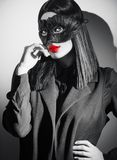 Beauty brunette woman portrait. Girl wearing carnival black feather mask pointing hand, proposing products royalty free stock photography