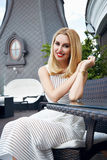 Beauty business woman in restaurant in white fashion dress. Beautiful young blonde woman with make-up in a restaurant café or bar, breakfast or supper came to stock photos