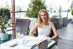 Beauty sexy business woman in restaurant in white fashion dress Royalty Free Stock Photography