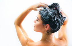 Beauty sexy model girl taking shower. And washing her long black hair with a shampoo Stock Photography