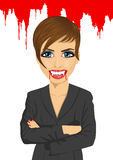 Beauty sexy vampire businesswoman standing over flowing blood Royalty Free Stock Images