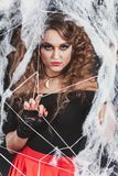 Beauty Witch girl caught in a spider web. Fashion Art design. Beautiful Gothic model girl with Halloween make up. And costume stock photography