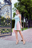 Beauty woman fashion model glamour style clothes. Casual dress for party and office accessory lather bag and silk wrap brand sunglasses street look garden yard royalty free stock photo
