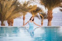 Beauty sexy Woman in swimwear posing and relax at the swimming pool with palms and sea on background at luxury resort. Summer voca. Beauty sexy Woman posing and Royalty Free Stock Photo