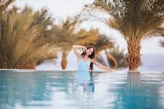 Beauty sexy Woman in swimwear posing and relax at the swimming pool with palms and sea on background at luxury resort. Summer voca. Beauty sexy Woman posing and Royalty Free Stock Photos