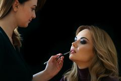 Beauty shop. Make up. Stylish paints lips with a brush to client. Royalty Free Stock Images