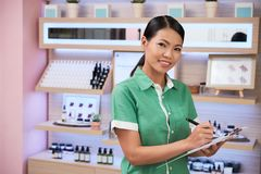 Beauty shop owner. Portrait of pretty young cosmetics shop owner with document stock photo