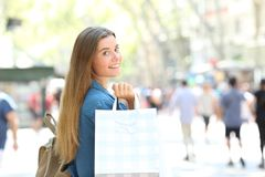 Beauty shopper showing shopping bags in the street. Beauty shopper showing blank shopping bags walking in the street Royalty Free Stock Photo