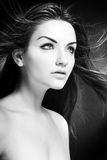 Beauty Shot. A beauty shot of a young blue eyed woman with her hair flowing in the wind. Black and white Royalty Free Stock Photos