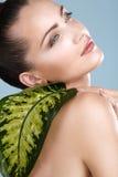 Beauty shot of beautiful woman looking trough leaf Stock Photo