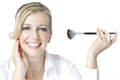 Beauty shot of Caucasian woman with make-up brush. Studio beauty shot of blonde Caucasian woman holding make-up brush and looking into camera isolated in white Royalty Free Stock Photos