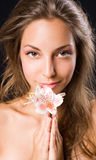 Beauty shot of gorgeous brunette holding flower. Royalty Free Stock Photography