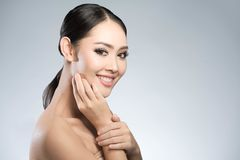 Beauty shot of young pretty asian woman with clear skin ongrey b. Ackground, for skin ad and cosmetology Stock Images