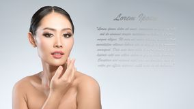Beauty shot of young pretty asian woman with clear skin ongrey b. Ackground, for skin ad and cosmetology with copy space for text insertion Stock Images