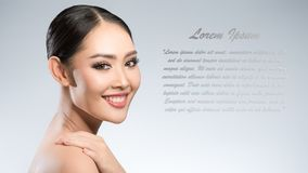 Beauty shot of young pretty asian woman with clear skin ongrey b. Ackground, for skin ad and cosmetology with copy space for text insertion Royalty Free Stock Photo