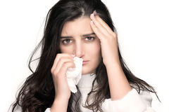 Beauty Sick Young Woman with Flu or Allergy. Portrait of beautiful brunette with headache and blows her nose into a tissue over white background Stock Photography