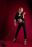 Beauty singer in black leather on red with mic Stock Images