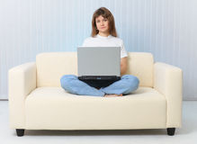 Beauty is sitting on couch with laptop Royalty Free Stock Image