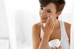 Beauty Skin Care. Beautiful Woman Applying Cosmetic Face Cream. Beauty Skin Care. Beautiful Happy Woman Applying Cosmetic Cream On Clean Face. Closeup Portrait Royalty Free Stock Photography