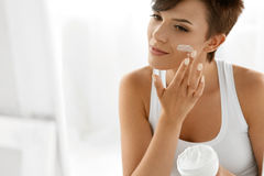 Beauty Skin Care. Beautiful Woman Applying Cosmetic Face Cream Royalty Free Stock Photography