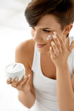 Beauty Skin Care. Beautiful Woman Applying Cosmetic Face Cream Stock Photos