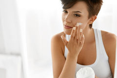 Beauty Skin Care. Beautiful Woman Applying Cosmetic Face Cream. Beauty Skin Care. Beautiful Happy Woman Applying Cosmetic Cream On Clean Face. Closeup Portrait Stock Photo