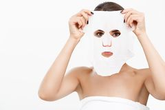 Beauty Skin Care Concept - Beautiful Caucasian Woman applying paper sheet mask on her face white background. Beauty Skin Care Concept - Beautiful Caucasian Stock Image